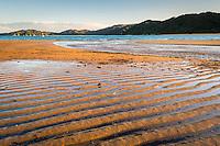 Sun sets on golden beach in Totaranui, Abel Tasman National Park, Nelson Region, New Zealand