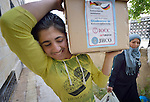 Refugees from Syria carry a box of household supplies home in Amman, Jordan, where they are not permitted to work. They received the box from International Orthodox Christian Charities, a member of the ACT Alliance.