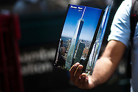 A woman sells a book with images of the World Trade Center while it has reached 1,776 feet, what makes it, the tallest building in the Western Hemisphere in New York,  May 10, 2013, Photo by Eduardo Munoz Alvarez / VIEWpress.