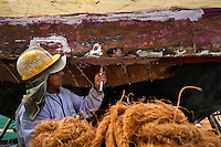An Ecuadorian worker caulks a traditional wooden fishing vessel, inserting hemp fiber between planks of the ship's shell, in an artisanal shipyard on the beach in Manta, Ecuador, 8 September 2012. The construction process takes 3-4 months to complete, depending on the ship size and purpose (fish capture methods). Although a wooden boat tends to be more stable on the sea and less expensive to build (up to $0.5 million USD), it needs a maintenance every 2 years, while a fiberglass-made boat, costing almost double the wooden one, may serve 5-6 years without any repairs. The shipyard produces 6-8 vessels every year.