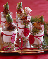 Hyacinth bulbs in individual glasses filled with pebbles are used as imaginative place settings for a Christmas table