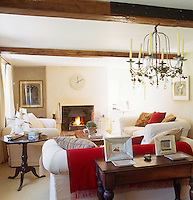 This country living room is comfortably furnished with splashes of bright colour added to the white sofas in the shape of cushions and a red blanket