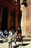 "Jordan. Petra. The archeological site is part of the UNESCO world heritage project.  The Nabataeans were an arabian industrious tribe which settled down in southern Jordan 2000 years ago. Petra is located at the bottom of a spectacular deep gorge surrounded by mountains. After walking down the ""Siq"", a narrow and long path through a fault due to a prehistoric earthquake, tourists discover the fist building ""El Khazneh"". Its high façade is carved in the rocks.  German tourists enjoy a camel ride. © 2002 Didier Ruef"