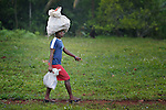 A woman, loaded down, walks along a path in Mizak, a small village in the south of Haiti.