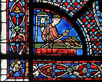 A grocer in his shop holds a belt and displays baskets of green and red fruits, from the donor window of the grocers, from the Life of St Nicholas stained glass window, 13th century, in the North aisle of the nave of Chartres cathedral, Eure-et-Loir, France. St Nicholas, 270-343 AD, was born in Patara in Lycia (now Turkey) and was bishop of Myra. Chartres cathedral was built 1194-1250 and is a fine example of Gothic architecture. Most of its windows date from 1205-40 although a few earlier 12th century examples are also intact. It was declared a UNESCO World Heritage Site in 1979. Picture by Manuel Cohen