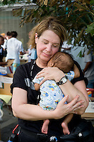 Devastation after the January 12, 2010 earthquake.  Volunteer with medical unit holding a baby <br />  at Sacre Couer, or CDTI Hospital. 2/3/10