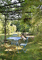 Tables and chairs are dotted around a garden lawn, some are shaded by foliage trailing over a pergola.