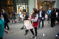 Customers with their purchases outside the Uniqlo Flagship store on Fifth Avenue in New York on Friday, October 14, 2011.  The store is a staggering 89,000 square feet on multiple levels and is Fast Retailing's second store in the United States with a third opening next week in the Herald Square shopping district. The largest store on Fifth Avenue filled to the brim with affordable clothing it competes with stalwarts such as the Gap and Zara which are in the immediate proximity. Fast Retailing plans on opening 200 to 300 stores worldwide until 2020 and currently has 1000 stores. (© Richard B. Levine)