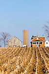 A small farmhouse amongst a harvested corn field on the northern Illinois plains.