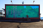 Escape? Two workmen exit a door in a mural depicting a forest in Barentsburg, a Russian coal mining town in the Norwegian Archipelego of Svalbard. Once home to about 2000 miners and their families, less than 500 people now live here. There are no trees in Svalbard.