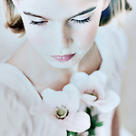 Young girl with pale features and blonde hair looking down wearing white dress holding flowers
