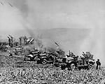 A line of Marine Corps rocket trucks launches a barrage of land-based, self-propelled rockets at the enemy during the Battle of Saipan.