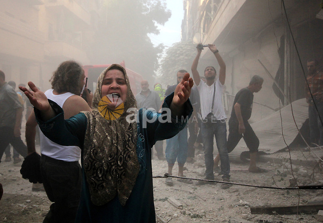 A Syrian woman mourns following an air strike by government forces on the al-Mowasalat neighbourhood of the northern Syrian city of Aleppo on September 20, 2015. Photo by Ameer al-Halbi