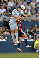 Matt Besler (5) defender Sporting KC beats Ryan Guy (13) midfield New England Revolution to the header..Sporting Kansas City and New England Revolution played to a 0-0 tie at LIVESTRONG Sporting Park, Kansas City, KS.