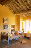 A pair of framed prints hangs above a cast-iron daybed and the sheer yellow curtains diffuse the afternoon sunlight