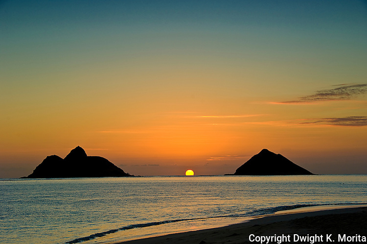 Fireball sunrise emerges from horizon between the Mokulua Islands in Lanikai Beach