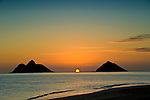 Fireball sunrise emerges from horizon between the Mokulua Islands in Lanikai Beach