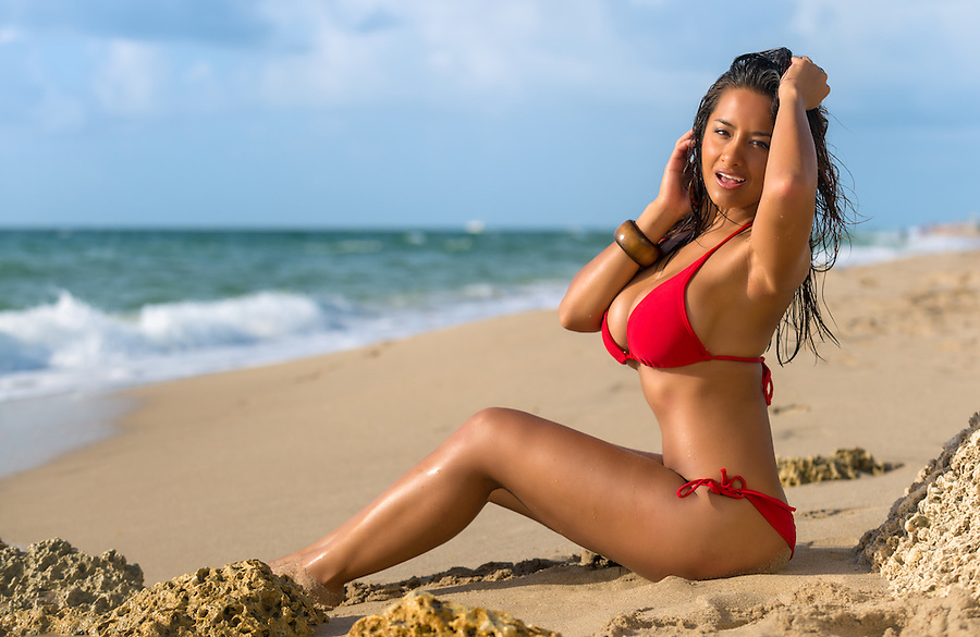 Portrait of hot female in red bikini sunbathing over the blurred beach background very happy