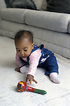 Berkeley, CA African American baby girl, seven months old, reaching for colorful rattle with ulnar grasp