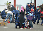 A refugee woman and her daughter laugh as Hungarian soldiers and police search them as they enter the country at Beremend, along Hungary's border with Croatia. Hundreds of thousands of refugees and migrants flowed through Hungary in 2015, on their way from Syria, Iraq and other countries to western Europe.