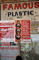 A boy points to a poster by the Dharavi Bachao Samiti organisation. The poster dipicts the politicians and developers of Dharavi as the three wise monkies. They feel that few of the slum dwellers will actually benefit from the development and are more likely to be eventually evicted in order to make way for flats for wealthy Mumbaikers.