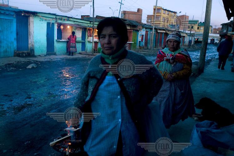 Women walk along a street in El Alto.