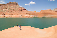 group of people on sandtone rocks above lake Powell
