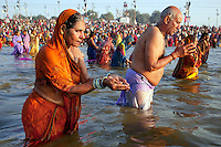 India. Uttar Pradesh state. Allahabad. Maha Kumbh Mela. An Indian Hindu devotee couple takes a holy dip at Sangam. The woman wearing a saree offers water to Mother Ganges (the river is a deity) and her husband prays. The Kumbh Mela, believed to be the largest religious gathering is held every 12 years on the banks of the 'Sangam'- the confluence of the holy rivers Ganga, Yamuna and the mythical Saraswati. In 2013, it is estimated that nearly 80 million devotees took a bath in the water of the holy river Ganges. The belief is that bathing and taking a holy dip will wash and free one from all the past sins, get salvation and paves the way for Moksha (meaning liberation from the cycle of Life, Death and Rebirth). Bathing in the holy waters of Ganga is believed to be most auspicious at the time of Kumbh Mela, because the water is charged with positive healing effects and enhanced with electromagnetic radiations of the Sun, Moon and Jupiter. The Maha (great) Kumbh Mela, which comes after 12 Purna Kumbh Mela, or 144 years, is always held at Allahabad. Uttar Pradesh (abbreviated U.P.) is a state located in northern India. 8.02.13 © 2013 Didier Ruef