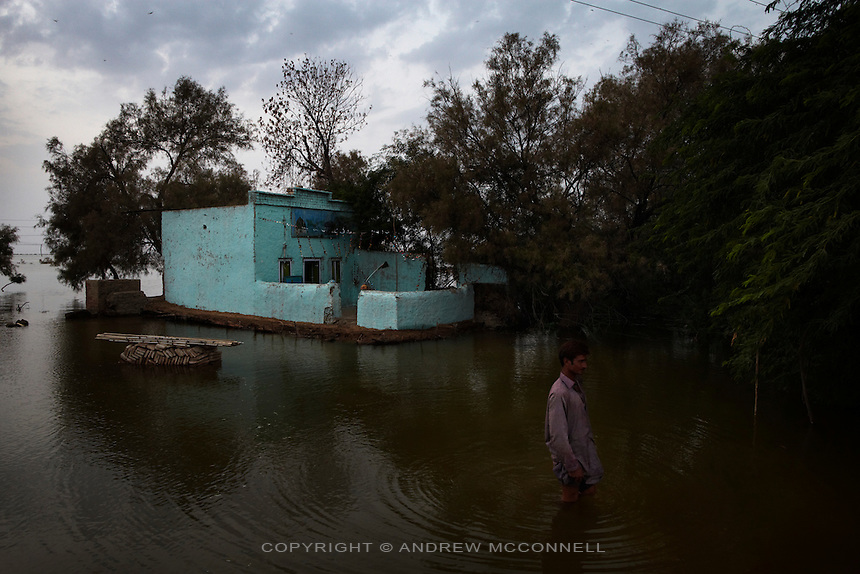A man wade through floodwater in the Jhanghara, Sindh province, Pakistan.