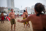 Tourists dance in the sand during a rainstorm, in Ipanema Beach, Rio de Janeiro, Brazil, on Sunday, Feb. 3, 2013.