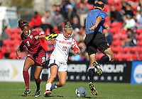 COLLEGE PARK, MD - OCTOBER 21, 2012:  Referee Bill Dittmer dances out of the way of Riley Barger (10) of the University of Maryland and Casey Short (3) of Florida State during an ACC women's match at Ludwig Field in College Park, MD. on October 21. Florida won 1-0.