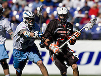 Sam Devore (44) of Johns Hopkins keeps a stick in the face of Rob Engelke (22) of Princeton during the Face-Off Classic in at M&T Stadium in Baltimore, MD