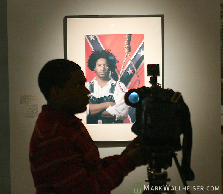 An African-American videographer with a local TV station videotapes the photograph Confederate Gothic that includes the artist John sims at an art show that includes the Confederate battle flag by artist John Sims at the Mary Brogan Museum of Art and Science  March 16, 2007.  (Mark Wallheiser/TallahasseeStock.com)