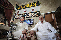 AMAD ASEID (ledt) and ALI JAMALU (right) the leader of all the committees and the leader of the security commettee at Taftanaz village respectively pose at the house office of the top committee of the local elected representation.