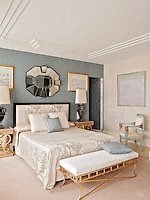 An elegant, luxurious bedroom in tones of blue grey and neutral furnishings. Two stylish lamps stand on bedside tables either side of a double bed with an upholstered headboard