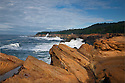 OR01180-00...OREGON - Rough surf pounding against the sandstone cliffs at Shore Acres State Park.