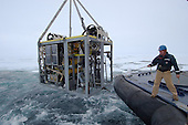 An under-ice research device being lowered into the Arctic Ocean. The 6200-pound steel-framed, open-sided box will be towed behind the icebreaker on a reinforced fiber-optic cable that relays commands down from and data up to the ship. It is equipped with camera and lighting systems, thrusters to maneuver and hover the over seafloor sites, and two hydraulically operated sampling systems.