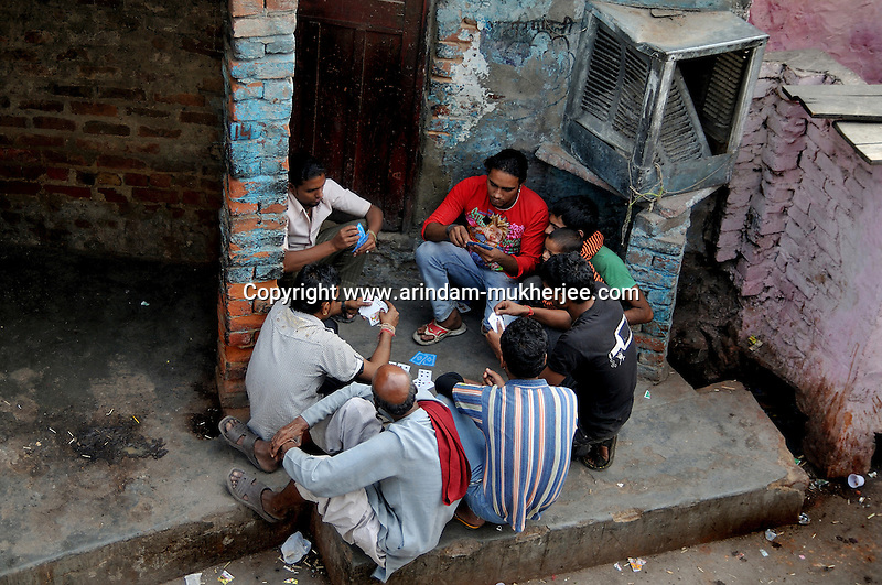 Young men playing cards at Katputly colony in New Delhi, India. 15.11.2009. Kathputly colony is a slum area in West Delhi. This slum seems like any other slum areas of modern India with dysfunctional electricity, non existing sanitation and poverty. As a part of Delhi, this is also ailed with water crisis. Large families live their lives crammed together in a single room with all the odds which complement poverty. One thing which differentiates this slum with any other is the people living in the colony. Nearly everybody in this slum is a traditional performing artist; and they have been migrating to this area for last 50 years from different parts of the country for a better livelihood. They are magicians, acrobats, jugglers, puppeteers, dancers and musicians. These artistes perform in star rated hotels, marriage ceremonies of the richer section, functions, and festivities all around the country and the world. Most of the artisans I met here, have performed in Europe and America but such opportunities are rare to come by. They struggle to keep their art form alive. They say that they don't get any help or support from the government for their basic needs and for the well being of the Kathputly colony -  though they have uphold the prestige of the country internationally. Polluted air, dirty alleys smelling of urine, colourful dress and sound of music characterise Kathputly colony, which is the one of its kind in India. Arindam Mukherjee