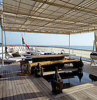 A large dining table under the canopy on Alberti Ferretti's houseboat
