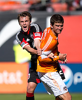 Bobby Boswell (32) of the Houston Dynamo is grabbed in the box by Jared Jeffrey (25) of D.C. United during a Major League Soccer game at RFK Stadium in Washington, DC. D.C. United vs. Houston Dynamo, 2-1.