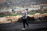 A female Palestinian protester uses a sling shot to throw stones towards Israeli security forces during clashes following the funeral of Ahmed Abu al-Aish, 28, and Laith Manasrah, 21, in Beit El on the outskirts of the West Bank city of Ramallah, Nov. 16, 2015. Two Palestinians were killed and three wounded in clashes with Israeli troops early Monday in a Palestinian refugee camp in the Jerusalem area, a Palestinian health official said. The Israeli military said its troops entered Qalandia to demolish the home of a Palestinian who it says shot and killed an Israeli motorist in the West Bank this summer after he stopped to give the Palestinian directions to a nearby spring. Photo by Shadi Hatem