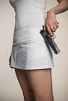 Caucasian woman holding handgun