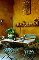 A simple metal folding table and chairs arranged in the crumbling splendour of the garden room of an 18th-century town house in Provence