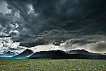 storm arives over spot mountain summer dark clouds with sun peaking though