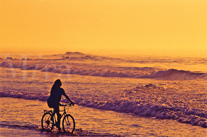 Woman riding bike along the beach at sunset.