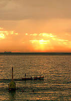 """The sun sets as Cottesloe surf boat crew row past the Cottesloe Beach pylon which they have painted """"Cott 05"""""""