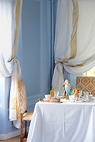 Gold-edged swagged curtains at the dining room windows create an air of opulence