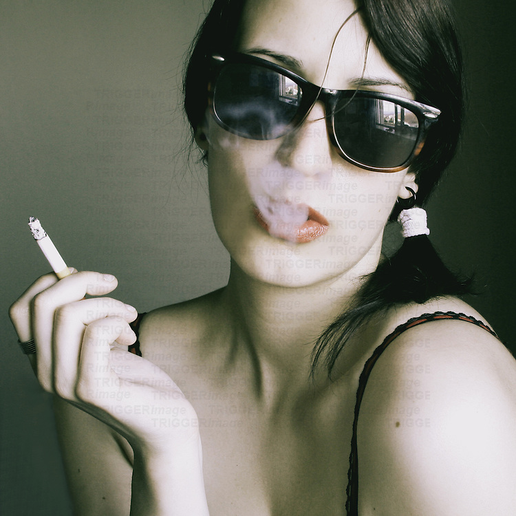 Close-up portrait of a young woman with pale skin and dark sunglasses, smoking a cigarette, in vintage tones.