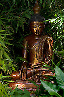 A Buddha copied from one in a temple in Pagan, Burma nestles amongst the foliage in the garden