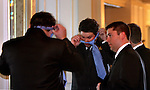 A groomsman gets tie tying assistance from another as the ceremony time nears.